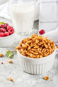 Ingredientes saludables para el desayuno. desayuno cereal leche o yogur frambuesas de vidrio y menta sobre fondo de piedra gris