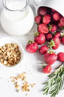 Ingredientes saludables para el desayuno. granola casera, leche o yogurt en jarras, fresas y romero