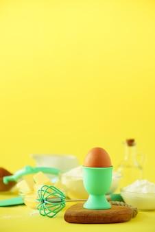 Ingredientes saludables para hornear - mantequilla, azúcar, harina, huevos, aceite, cuchara, cepillo, batidor, leche sobre fondo amarillo.