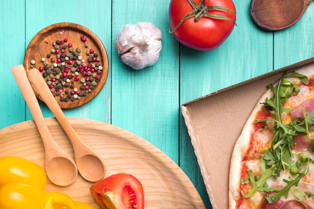 Ingredientes saludables en superficie con textura de madera con verduras y deliciosa pizza