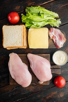 Ingredientes del sándwich club, sobre fondo de madera oscura, vista superior