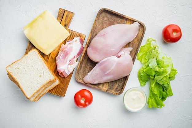 Ingredientes del sándwich club, sobre mesa blanca