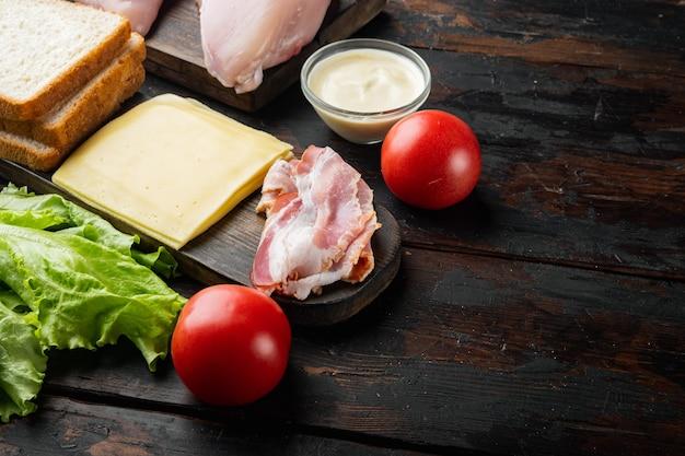 Ingredientes del sándwich club, sobre la mesa de madera antigua con espacio para copiar texto