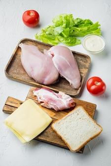 Ingredientes para sándwich, tocino, queso, tomate, carne de pollo, lechuga, salsa, sobre fondo blanco.