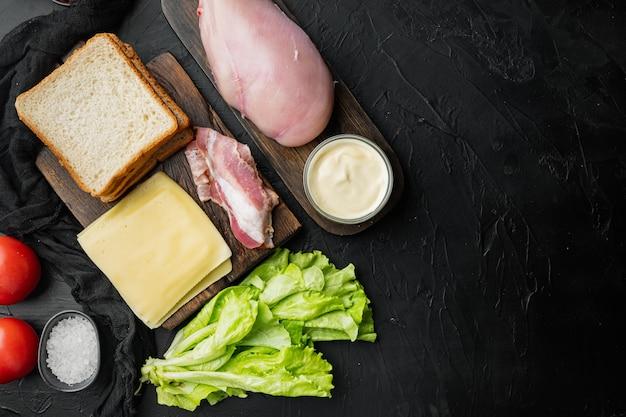 Ingredientes para sándwich, tocino, queso, tomate, carne de pollo, lechuga, salsa, sobre fondo negro, vista superior con espacio para copiar texto