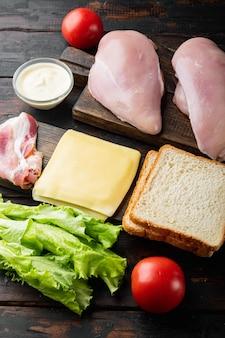 Ingredientes para sándwich, tocino, queso, tomate, carne de pollo, lechuga, salsa, sobre mesa de madera antigua