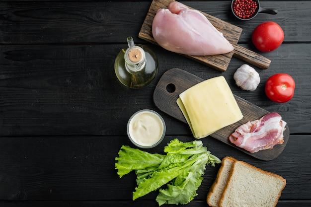 Ingredientes para sándwich, tocino, queso, tomate, carne de pollo, lechuga, salsa, sobre mesa de madera negra, vista superior con espacio para copiar texto
