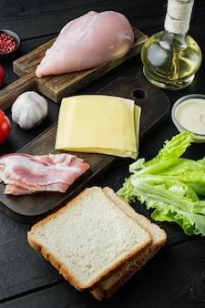 Ingredientes para sándwich, tocino, queso, tomate, carne de pollo, lechuga, salsa, sobre mesa de madera negra