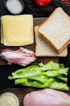 Ingredientes para sándwich, tocino, queso, tomate, carne de pollo, lechuga, salsa, sobre mesa negra, vista superior