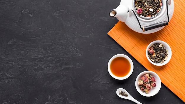 Ingredientes secos del té en un tazón de cerámica con una tetera en el mantel sobre una superficie negra