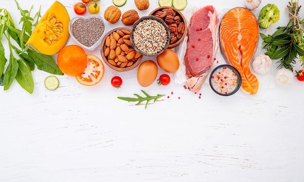 Ingredientes para la selección de alimentos saludables sobre fondo blanco de madera.