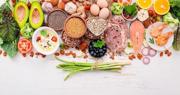 Ingredientes para la selección de alimentos saludables sobre fondo blanco de madera