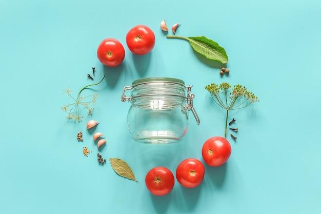 Ingredientes para tomates marinados y frascos de vidrio.
