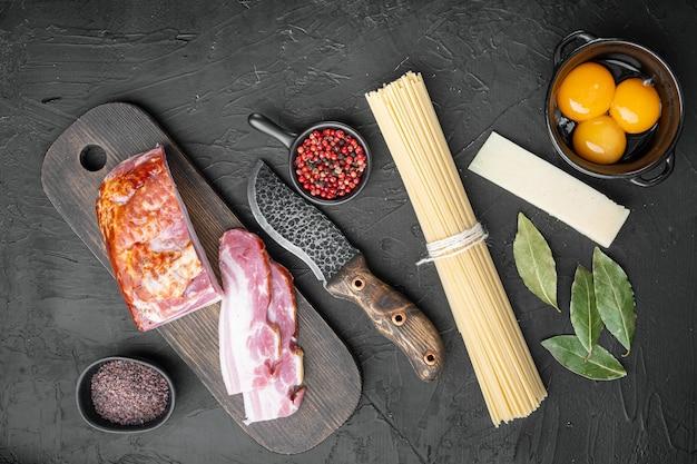 Ingredientes tradicionales de pasta carbonara italiana. tocino, espaguetis, parmesano y queso pecorino, huevo, ajo, sobre mesa de piedra negra, vista superior plana