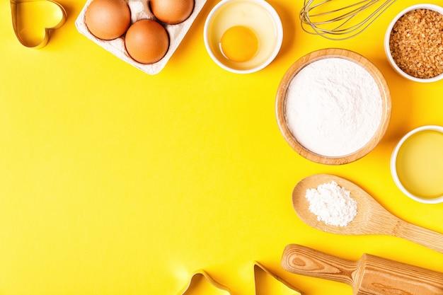 Ingredientes y utensilios para hornear sobre un fondo pastel, vista superior.