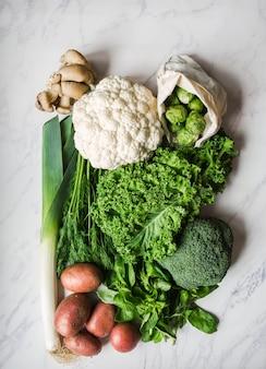 Ingredientes veganos saludables para cocinar. varias verduras y hierbas limpias en el fondo de mármol. productos del mercado sin plástico. lay flat