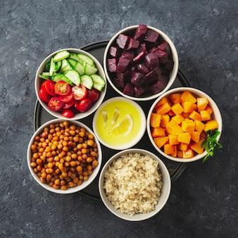 Ingredientes vegetarianos saludables para cocinar ensalada marroquí. garbanzos, calabaza al horno y remolacha, quinua y verduras vista superior espacio de copia