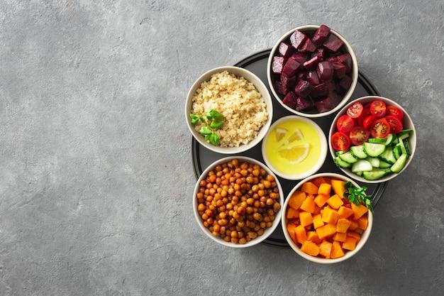 Ingredientes vegetarianos saludables para cocinar ensalada marroquí. garbanzos, calabaza al horno y remolacha, quinua y verduras.