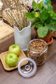 Ingridients para desayuno saludable, pudín de chía en mesa de madera. almendras, manzanas, anacardos, dátiles, cacao, granola.