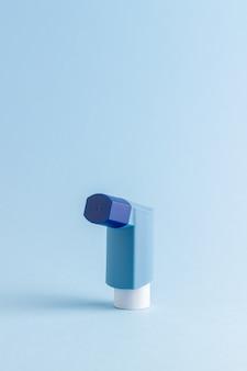 Inhalador sobre una mesa azul. medicamento. salud. enfermedades respiratorias.