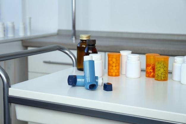 Inhaladores para el asma y medicamentos en la mesa.