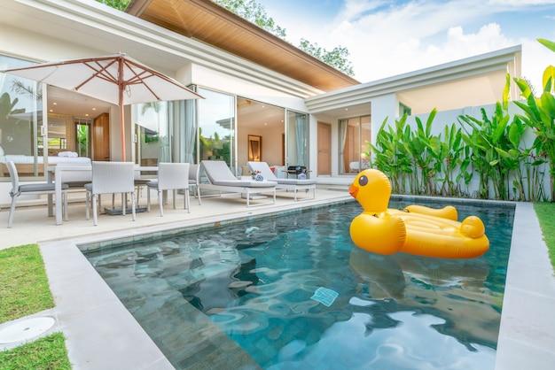 Inicio diseño de exteriores que muestra una villa con piscina tropical y jardín con vegetación.