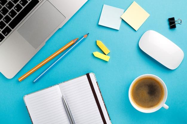 Inicio del escritorio de oficina de trabajo de la mañana con una taza de café computadora portátil, cuaderno, bolígrafo, mesa de textura azul. fondo del concepto de negocios