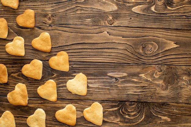 Inicio hornear galletas corazones. las galletas en forma de corazones se encuentran en diagonal sobre la mesa.