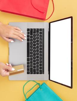 Inicio internet compras comercio electrónico manos femeninas con tarjeta de crédito mientras está sentado en una computadora portátil