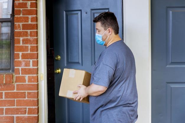 Inicio en línea pedir entrega de comida durante la cuarentena de la pandemia de coronavirus un hombre con una máscara médica con un paquete de caja en sus manos