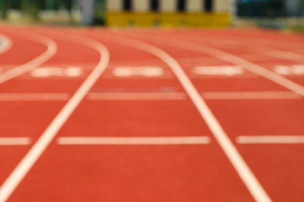 Inicio de pista atlética roja con números, fondo borroso