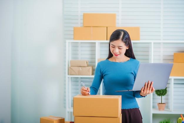 Inicio de propietario de negocio pyme joven escrito dirección del cliente a la caja.