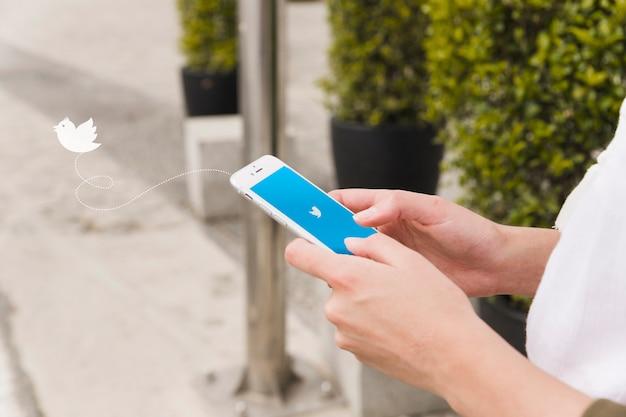 Inicio de sesión de mujer en la aplicación de twitter en el teléfono móvil