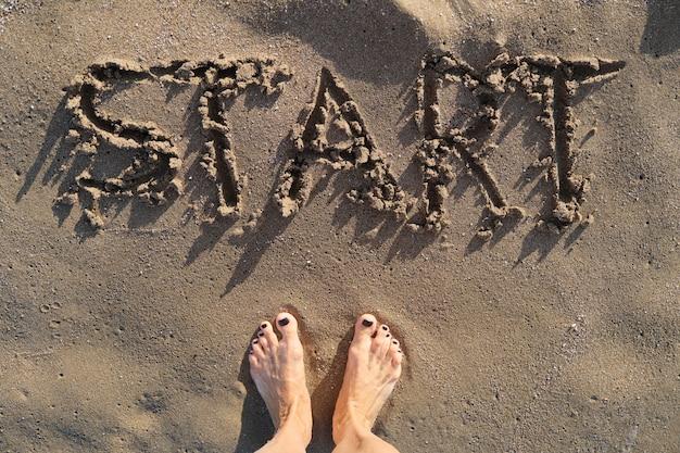 Inicio de texto escrito en la arena en la playa del mar y los pies descalzos de la mujer de pie delante de la palabra
