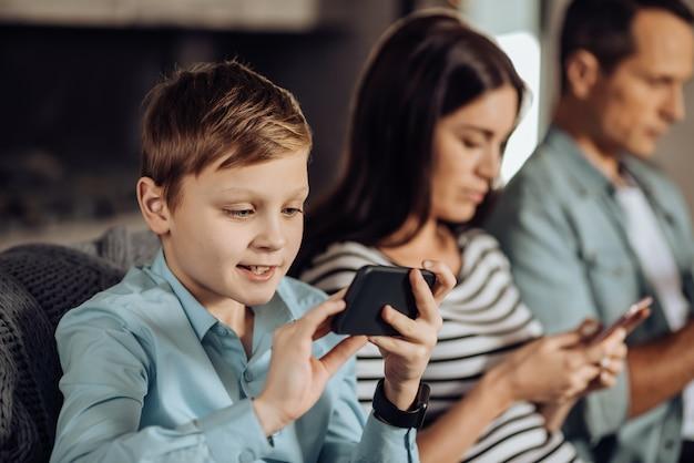 Inmerso en los juegos. la atención se centra en un agradable niño preadolescente que juega en el teléfono y sonríe con entusiasmo mientras sus padres se sientan a su lado y también usan sus teléfonos.