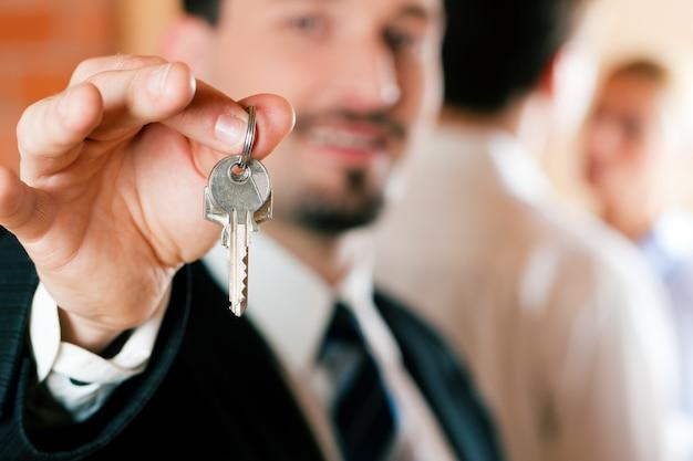 Inmobiliaria en apartamento dando llaves a pareja.