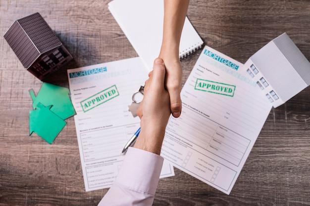 Inmobiliaria y cliente estrechar la mano de acuerdo
