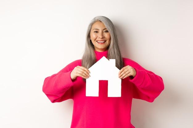 Inmobiliaria hermosa abuela asiática mostrando casa de papel y sonriendo feliz de pie en sudor rosa ...