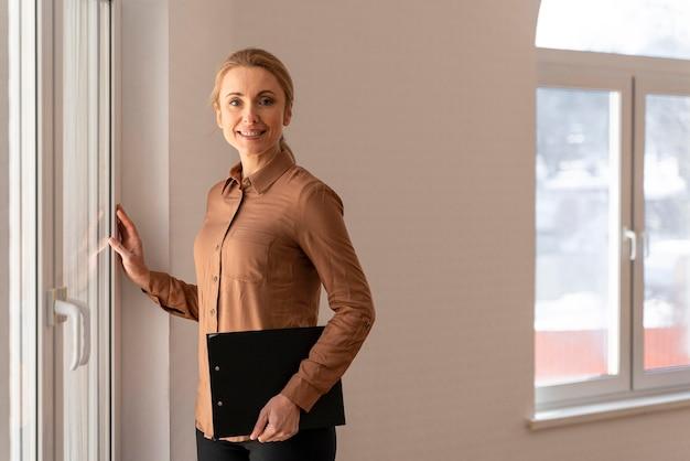Inmobiliaria mujer sonriente posando en casa vacía mientras sostiene el portapapeles