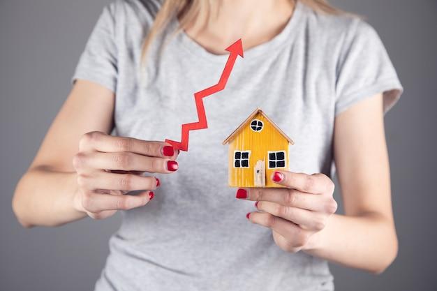 Inmobiliaria, mujer sosteniendo flecha y modelo de casa