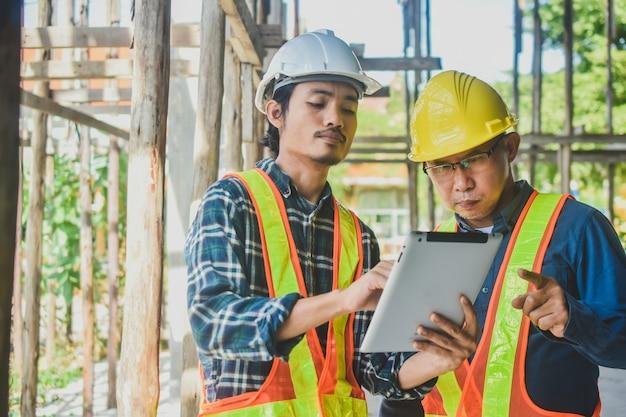 Inmobiliario de construcción de sitio de inspección de tableta de dos ingenieros