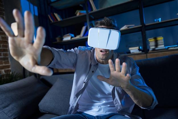 Innovador chico activo ambicioso sentado en un sofá y con gafas especiales mientras explora la realidad virtual