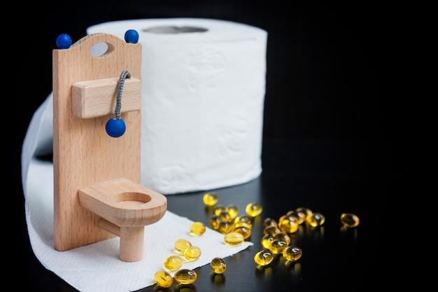Inodoro de juguete de madera, cápsulas y papel sobre negro