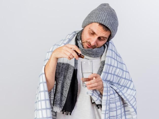 Insatisfecho joven enfermo con gorro de invierno y bufanda envuelto en plaid vertiendo medicamento en un vaso de agua aislado en blanco