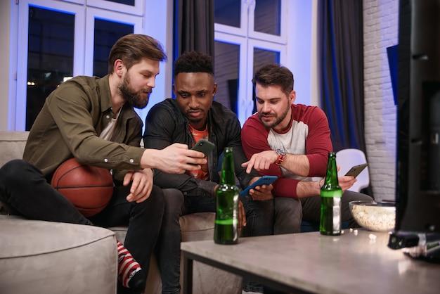Insatisfecho con el juego internacional de compañeros masculinos que beben cerveza y navegan por sus teléfonos inteligentes mientras miran el campeonato mundial en la televisión.