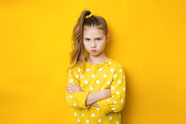 Insatisfecho ofendido niña adolescente triste con los brazos cruzados sobre fondo amarillo con espacio de copia