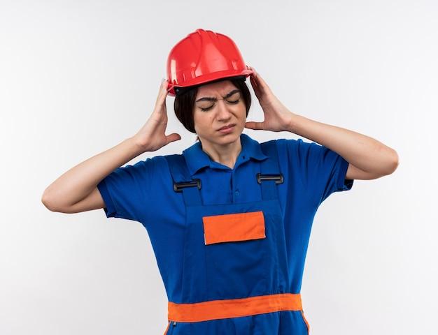 Insatisfecho con los ojos cerrados joven constructor mujer en uniforme tomados de la mano alrededor de la cabeza
