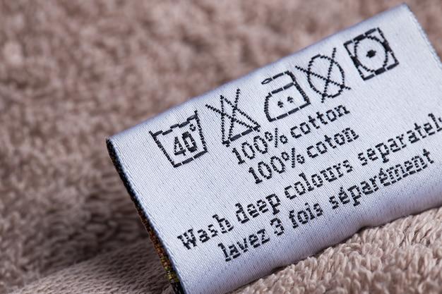 La inscripción 100% de los gatos en una toalla sobre un fondo rosa