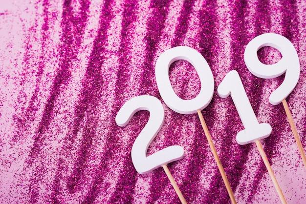 Inscripción 2019 en palitos con polvo de purpurina en mesa.