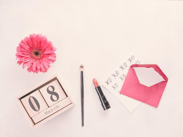 Inscripción del 8 de marzo en bloques de madera con flor y lápiz de labios en mesa